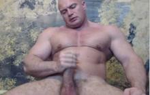 Bodybuilder flexing and stroking