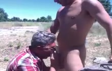 Sexy stud gets his big cock sucked by daddy outdoors